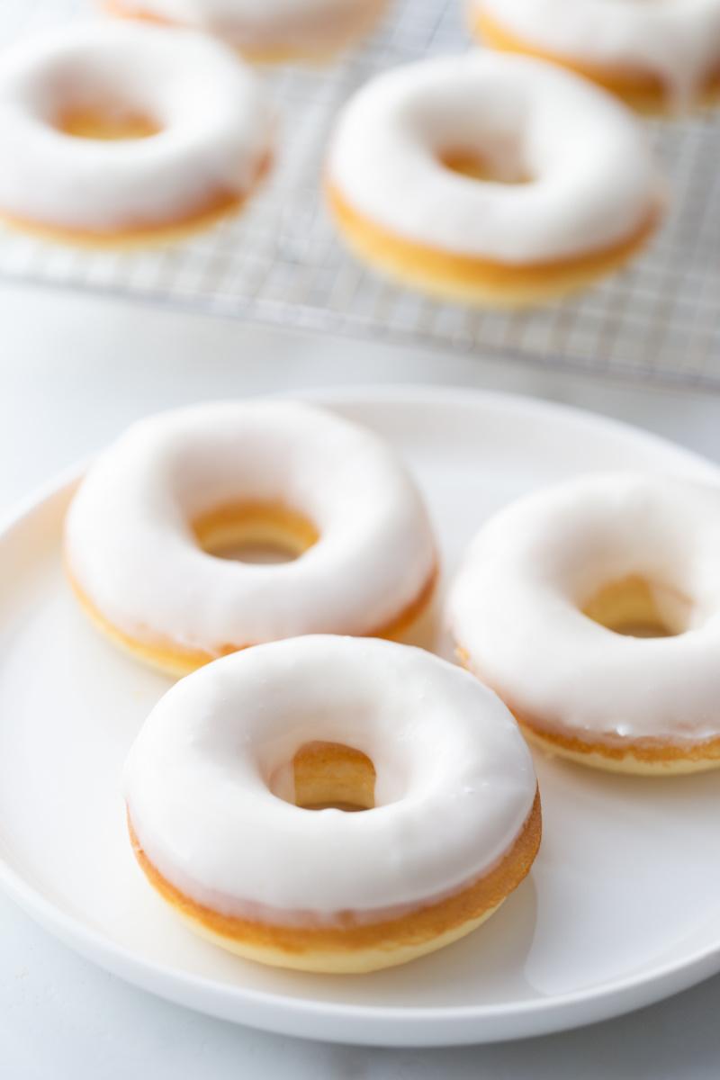 white glazed doughnuts on white plate