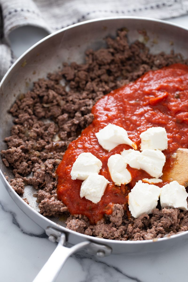 ground beef, tomato sauce and cheese in skillet