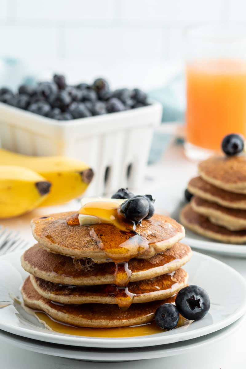 stack of banana blueberry blender pancakes with butter and syrup