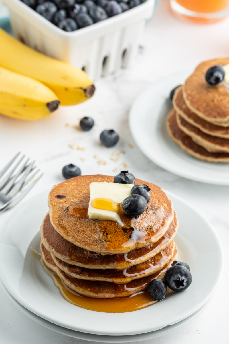 stack of blueberry pancakes with butter and syrup on top