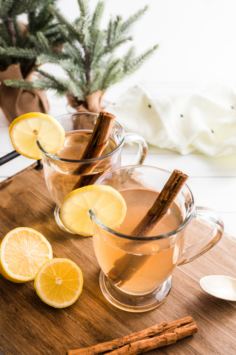 hot toddy in glass mugs with lemon and cinnamon stick