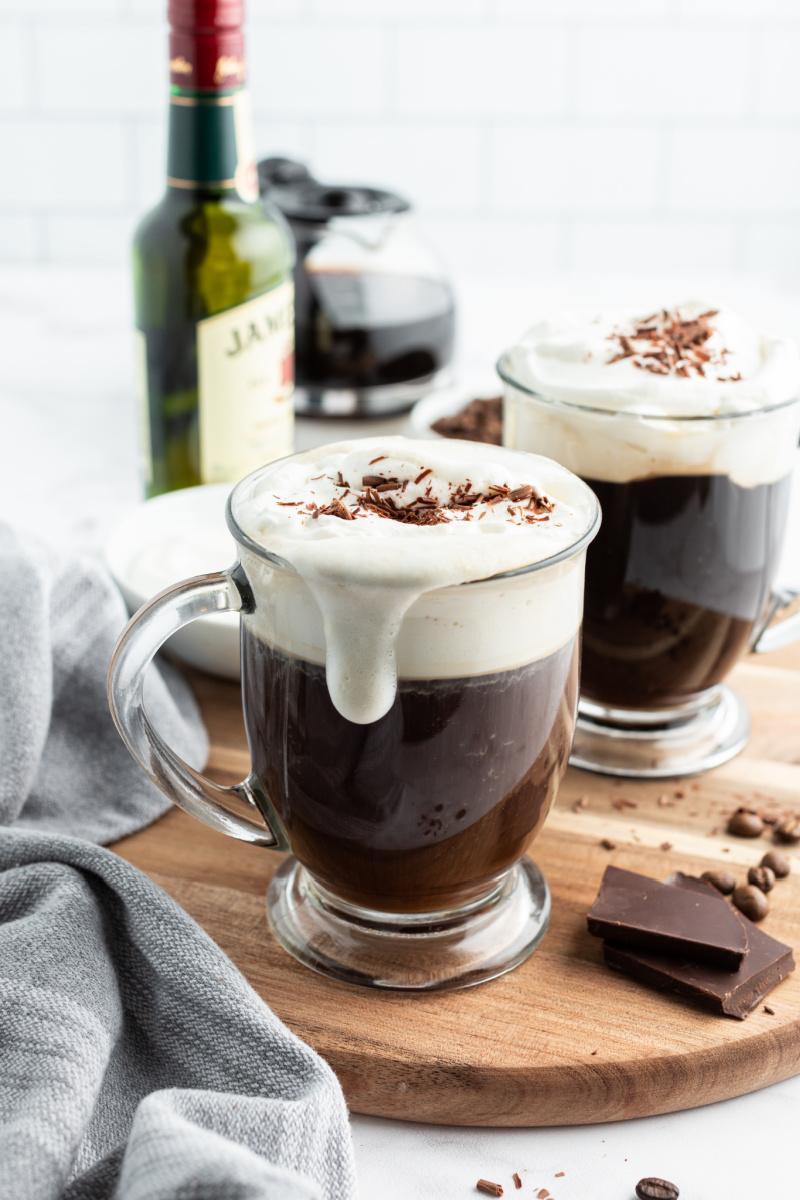 irish coffee in glass mug with foam drip down side