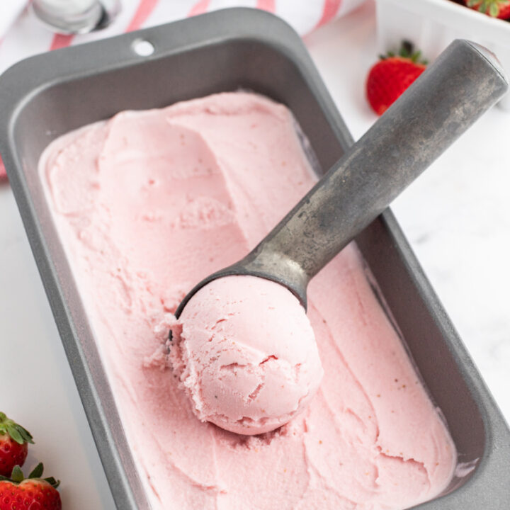 scooping strawberry ice cream out of a container