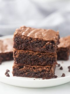 three brownies in a stack on a white plate