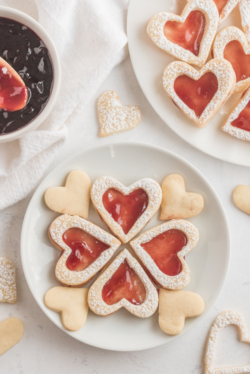 heart shaped raspberry linzer cookies on white plate