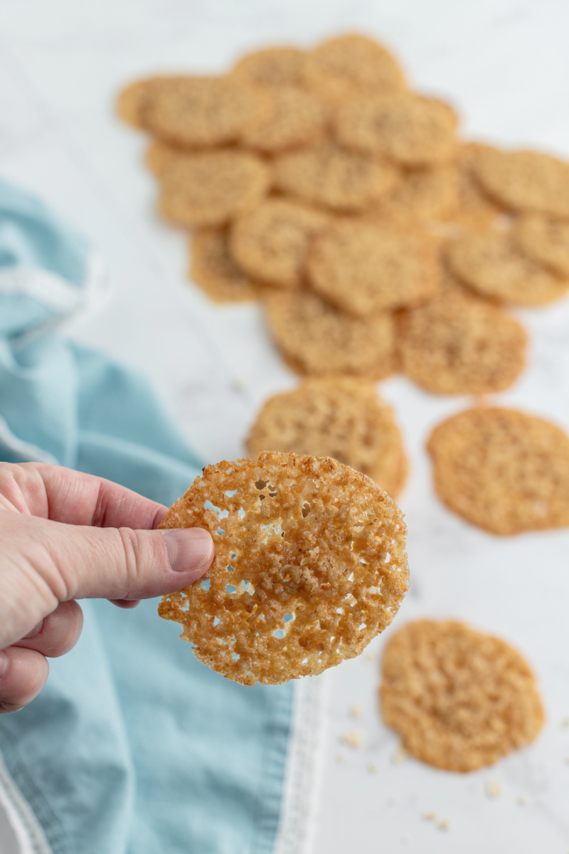 holding lacy oatmeal cookie