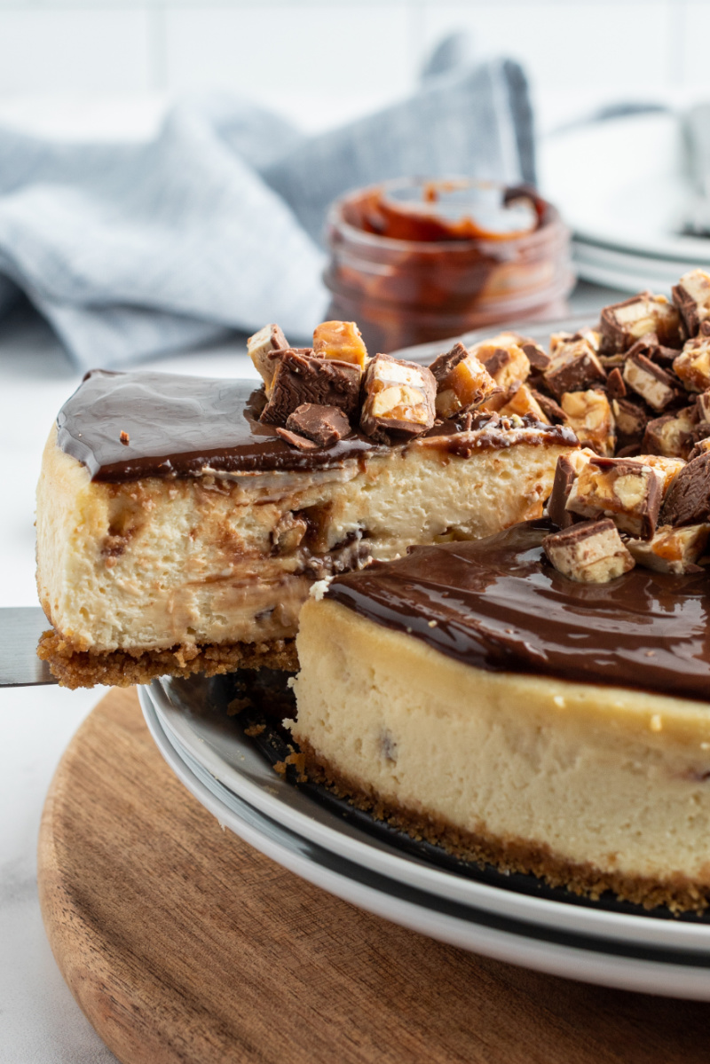 slice of white chocolate snickers cheesecake being removed from the whole cheesecake