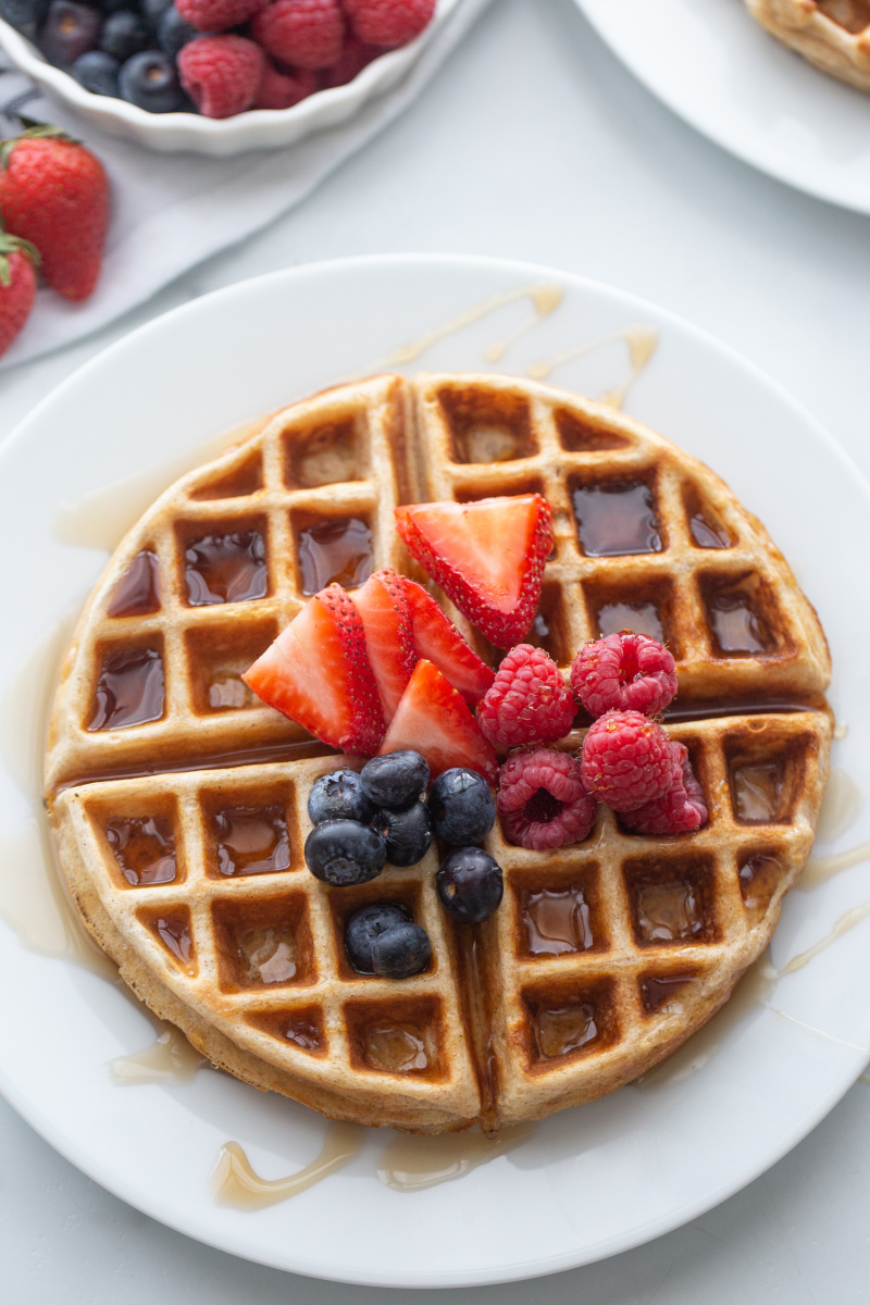 waffle on a white plate topped with syrup and berries