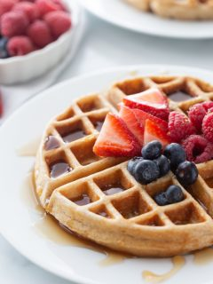 whole grain buttermilk waffle on white plate with syrup and berries