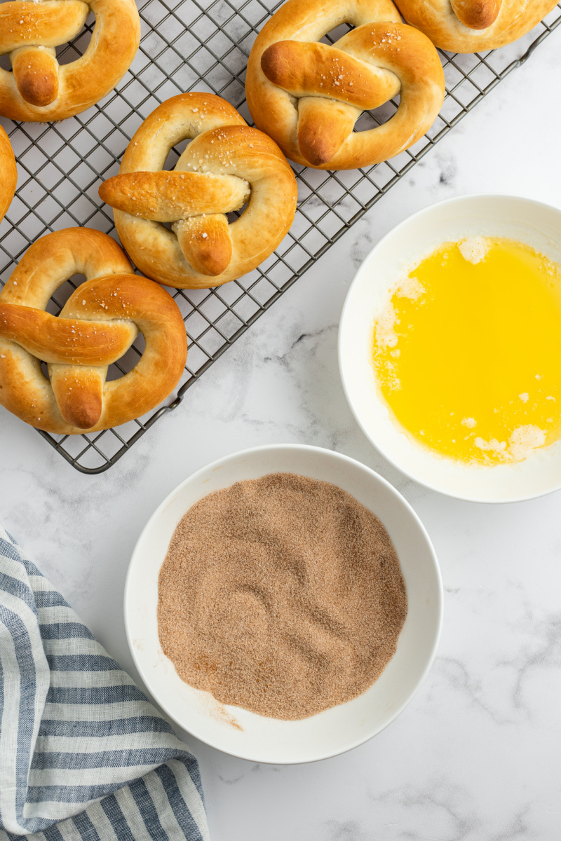 pretzels on a cooling rack ready to dip into butter, cinnamon and sugar