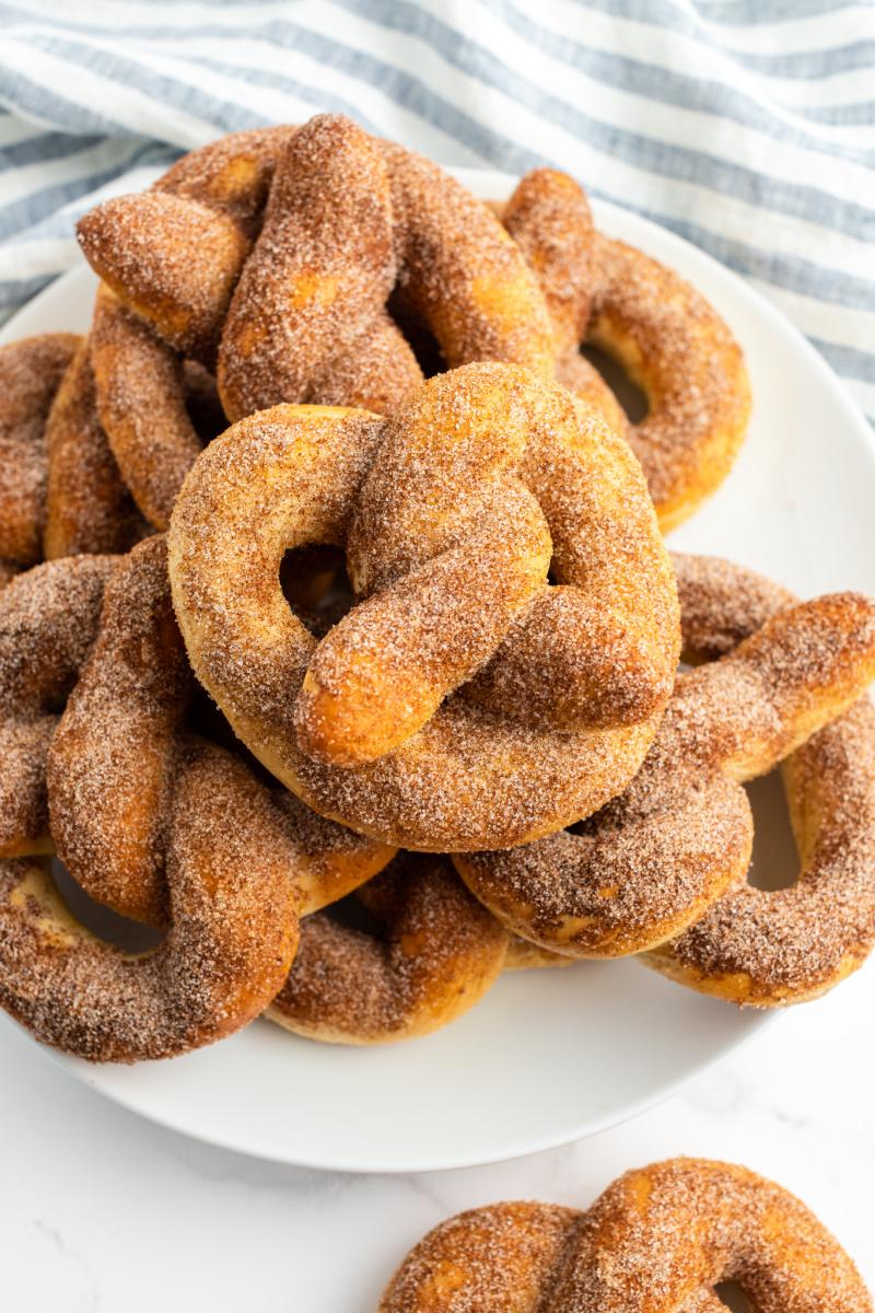cinnamon sugar soft pretzels stacked on a white platter