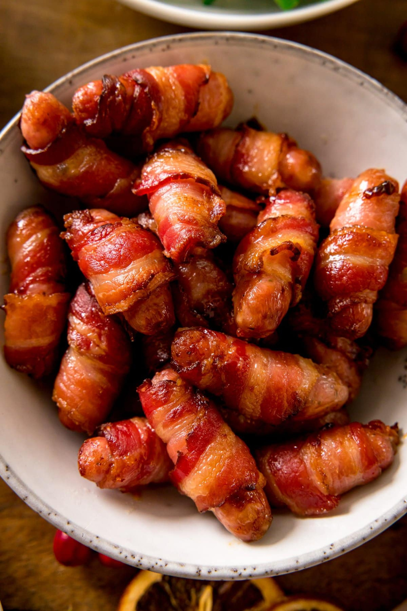 bacon wrapped pigs in a blanket in a white bowl