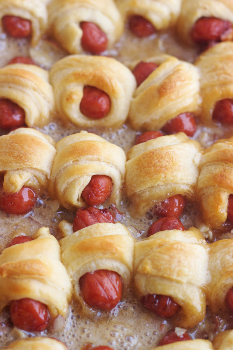 caramelized pigs in a blanket sizzling on a baking sheet