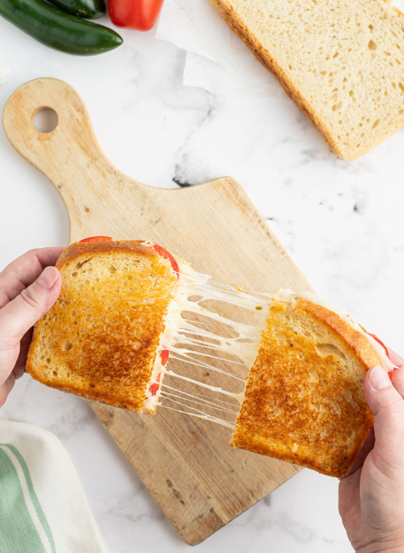 two hands pulling apart a grilled cheese sandwich to show melted cheese