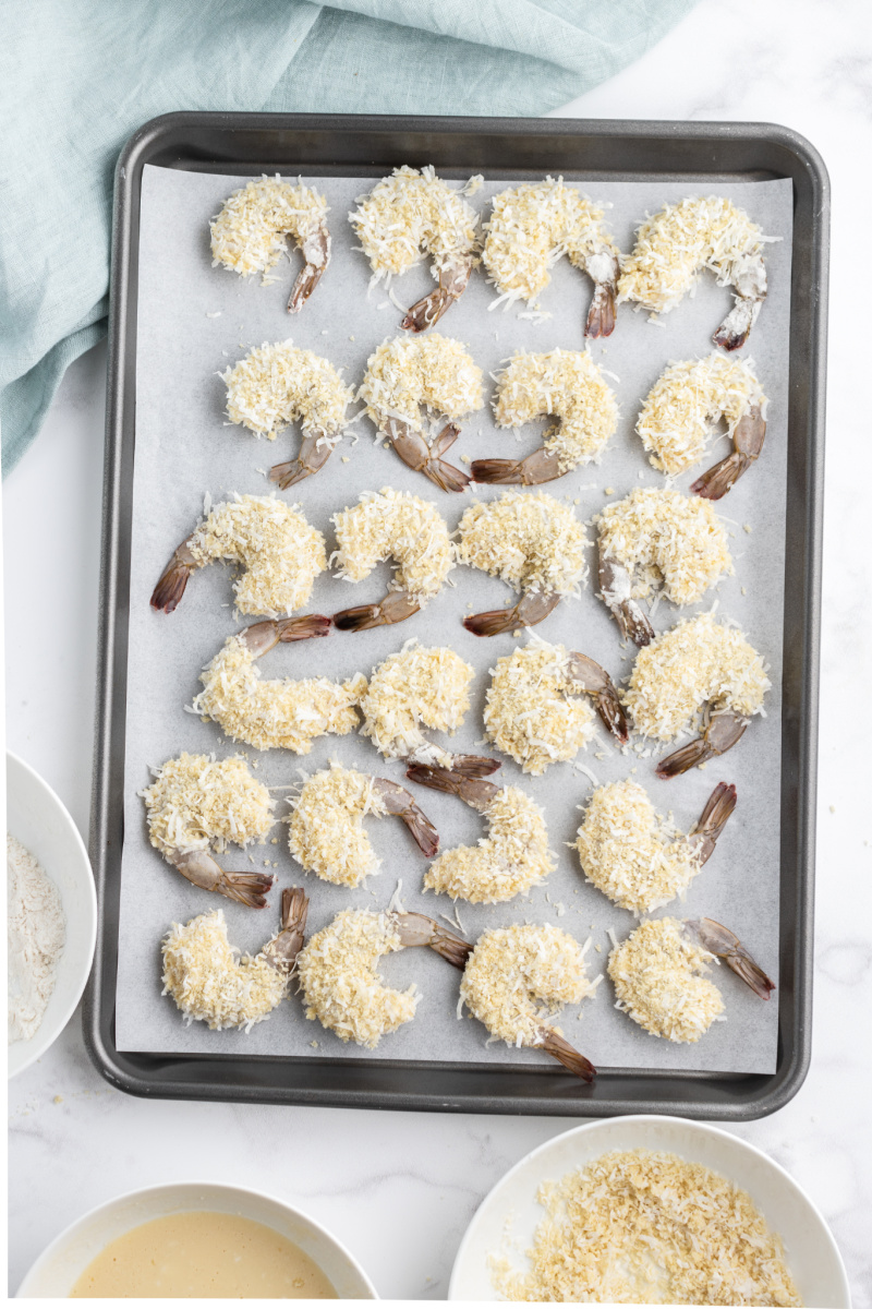coconut shrimp on a baking sheet ready for oven