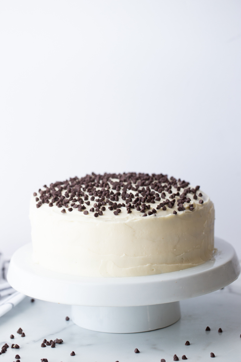 chocolate chip cheesecake cake on a white cake platter