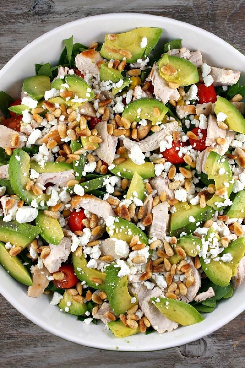 chicken spinach salad in white bowl