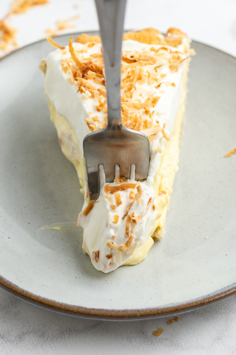 fork in a slice of coconut cream pie on a white plate