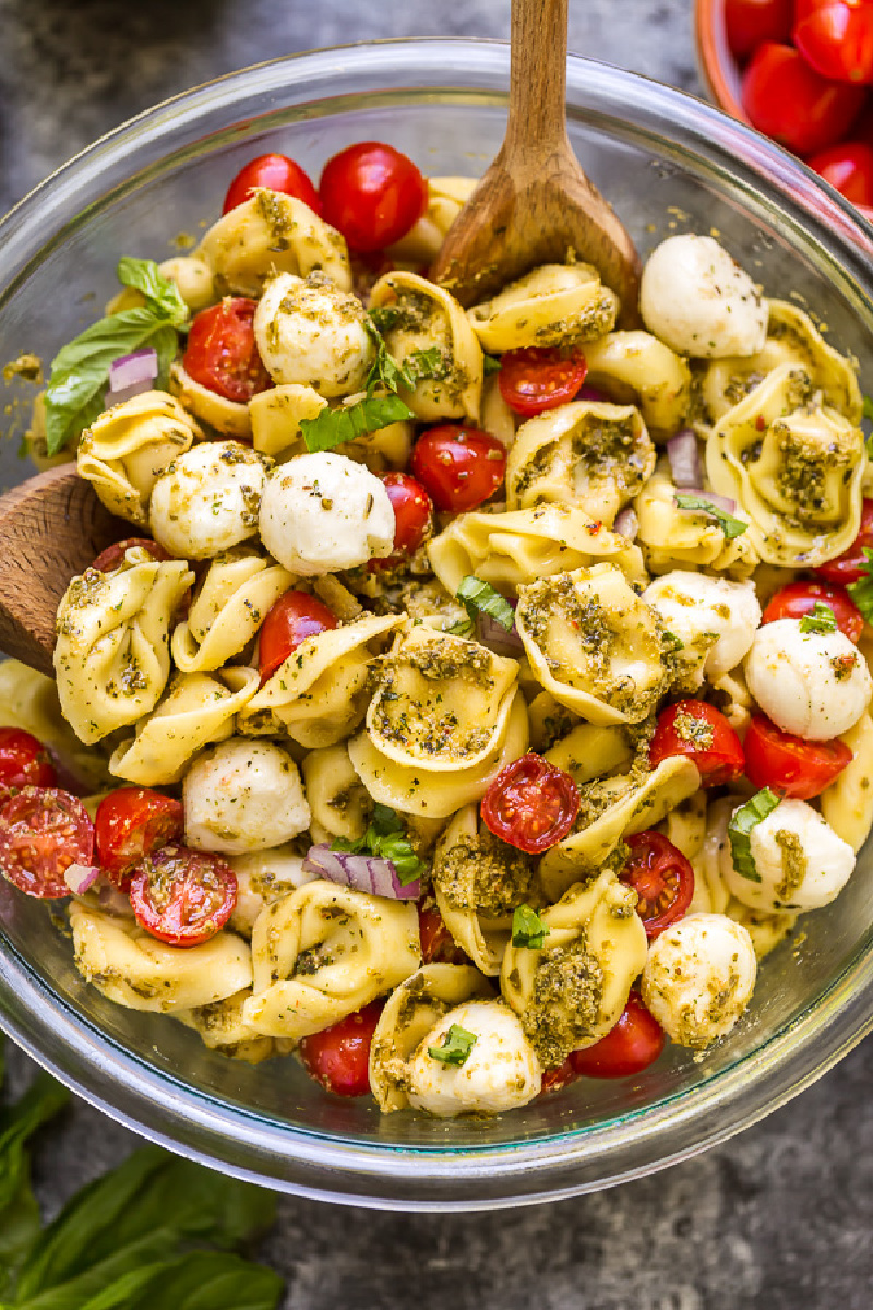 pesto tortellini salad in bowl with serving spoon