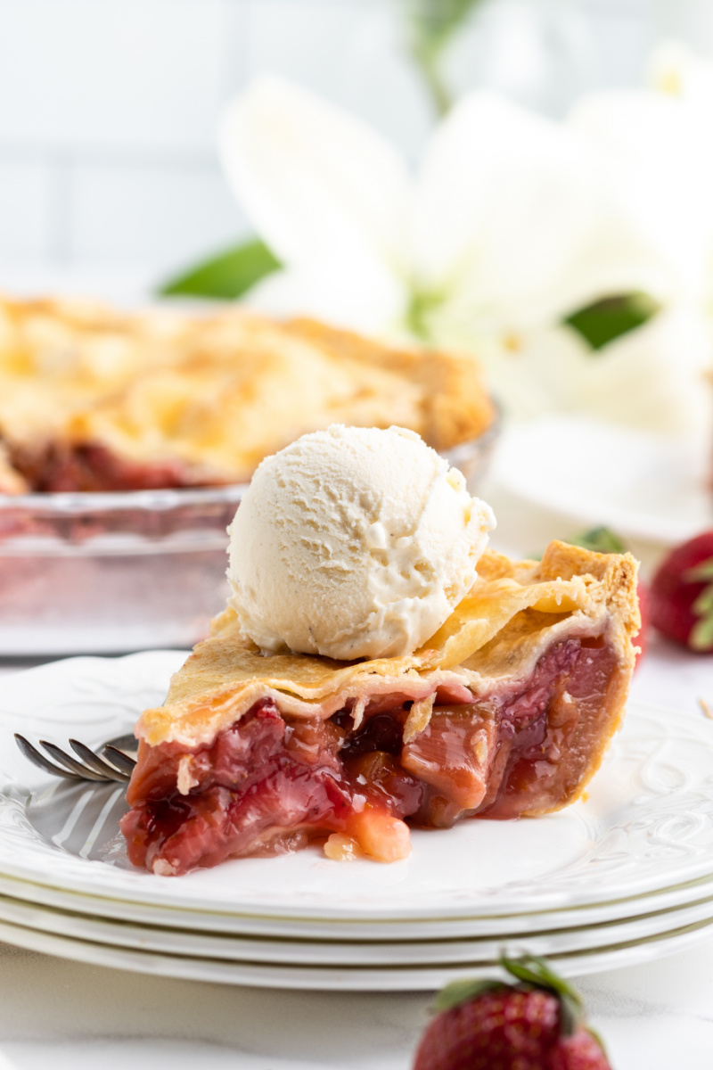 slice of strawberry rhubarb pie on a white plate topped with vanilla ice cream