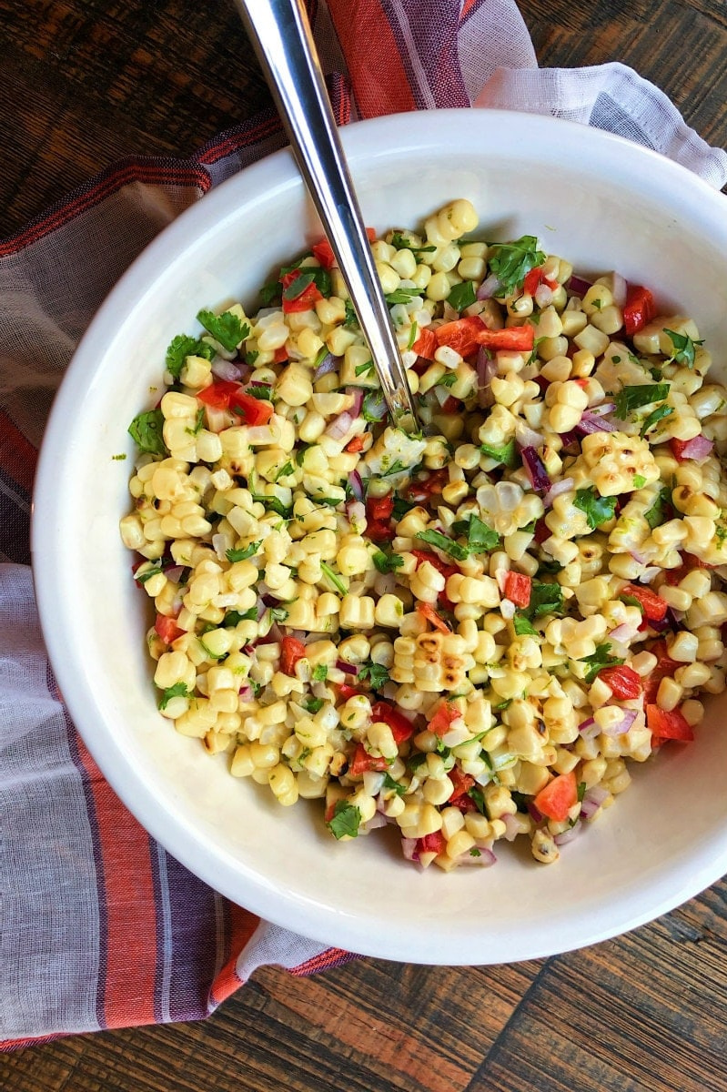 grilled corn salad in white bowl with serving spoon