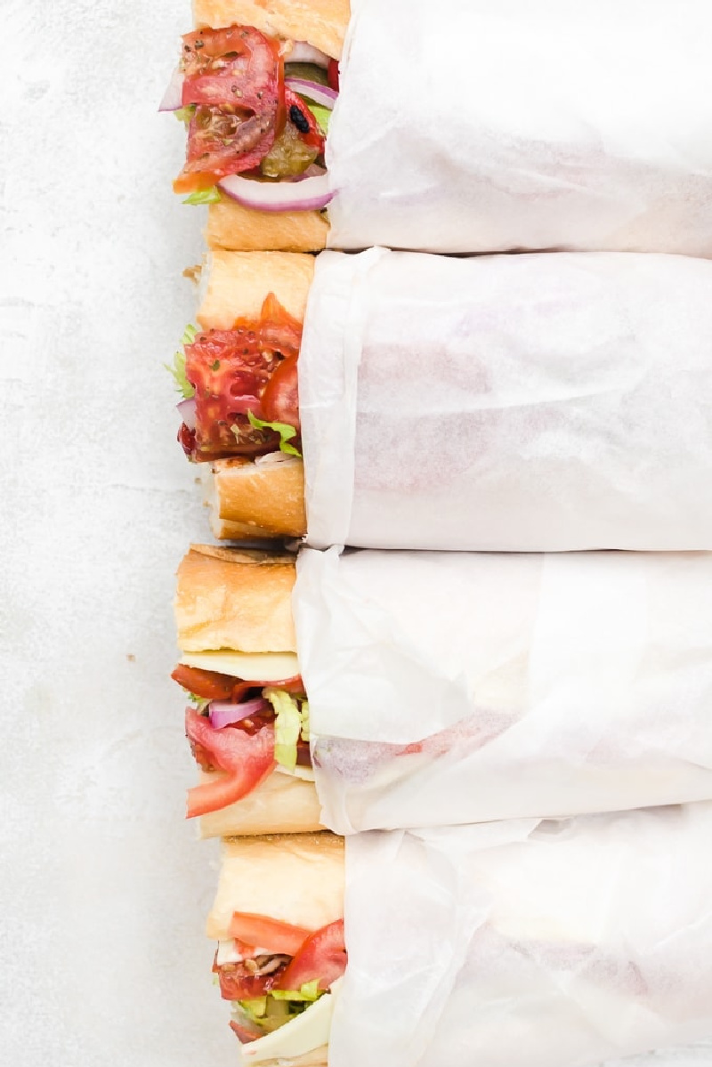 wrapped hoagies with a peek at the end of the sandwiches sticking out of the wrap