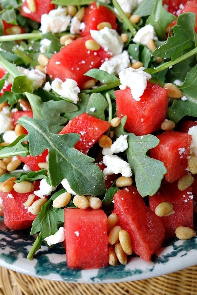 Watermelon feta and arugula salad in white bowl
