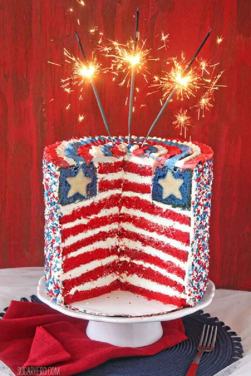 american flag layer cake sliced open with sparklers lit on top