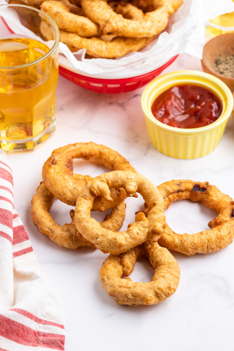 a few onion rings scattered on a table with ketchup