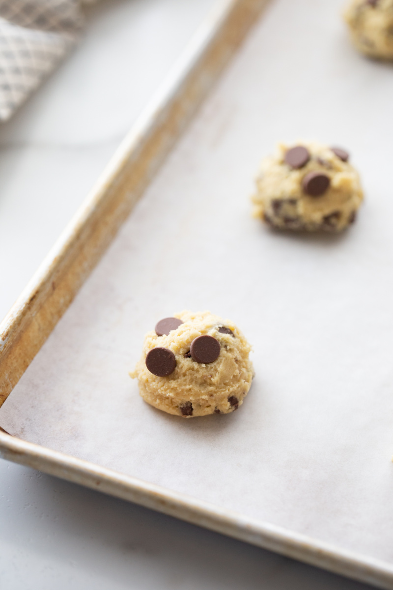 chocolate chip cookie dough on a baking sheet ready for oven