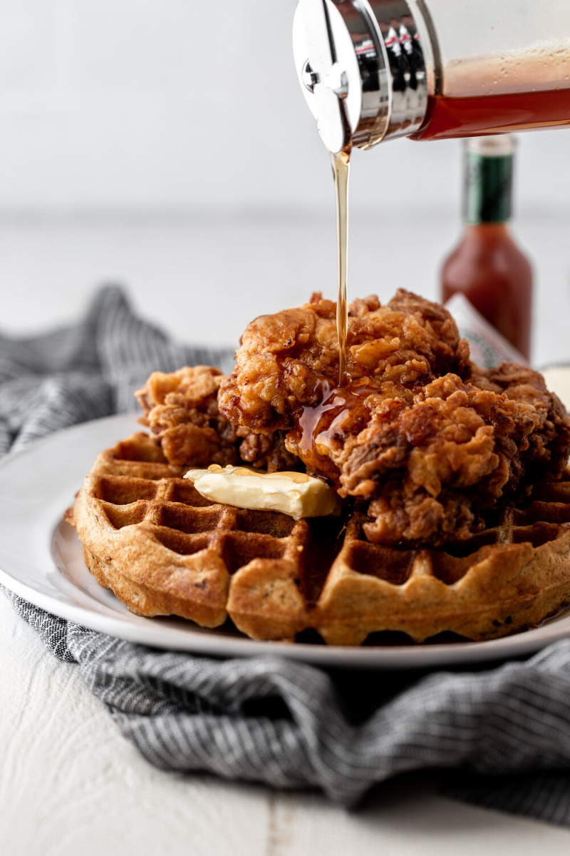 fried chicken and waffles with syrup poured over