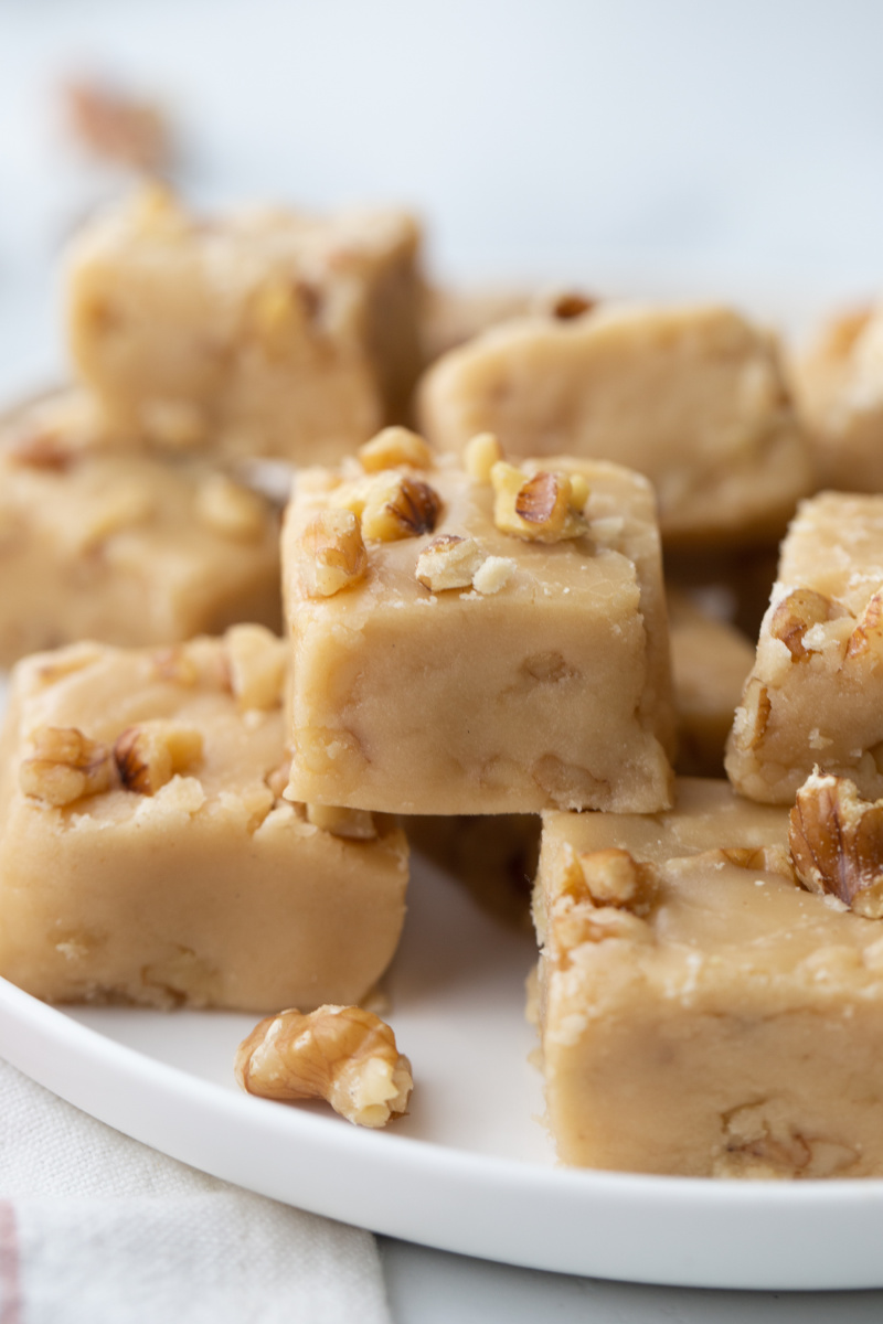 pieces of maple walnut fudge stacked on white platter