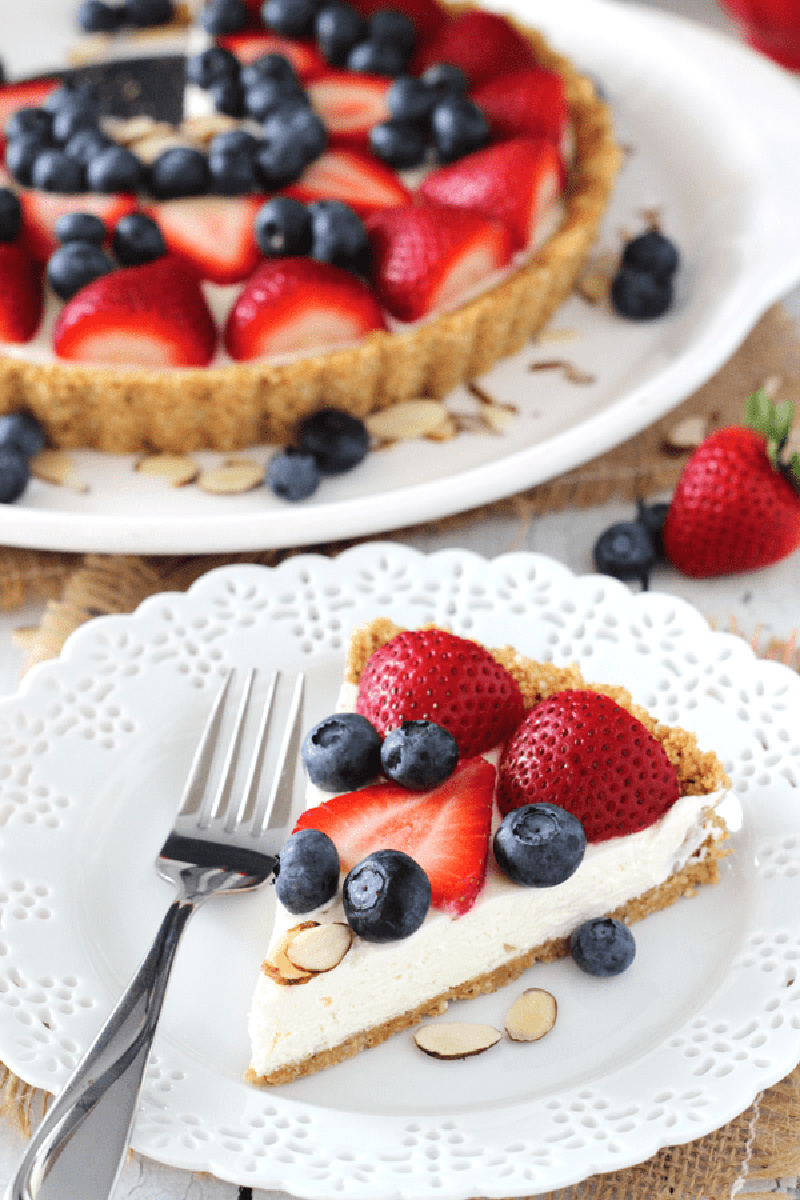 slice of berry almond tart with rest of tart displayed behind it