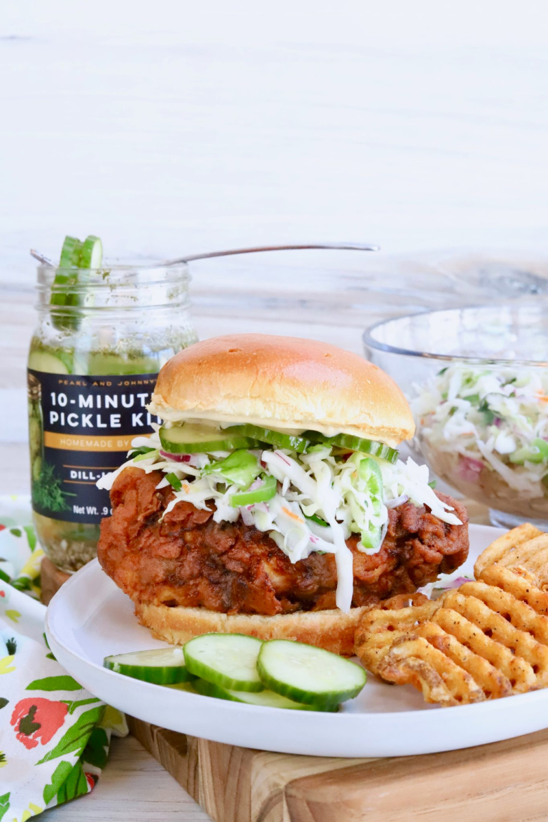 pickle juice crispy fried chicken sandwich on a plate with a pickle