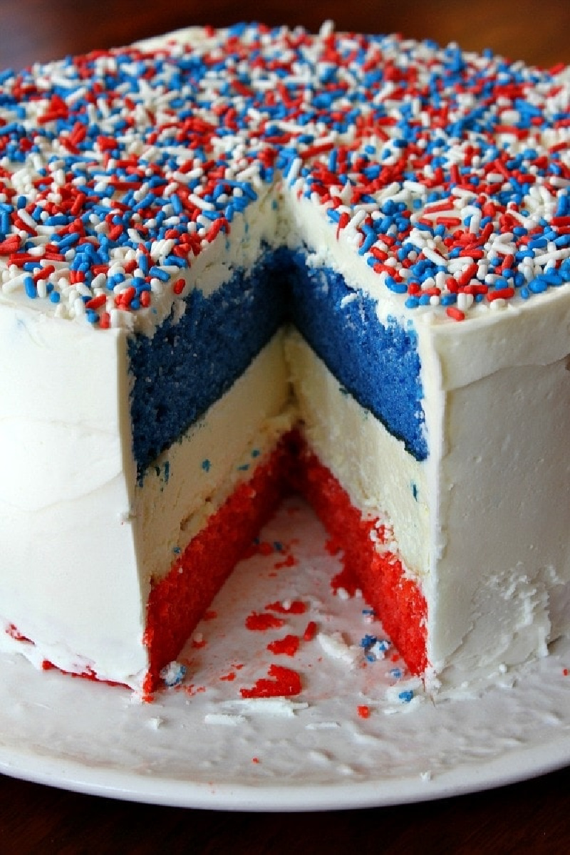 red white and blue cheesecake cake with slice taken out of it