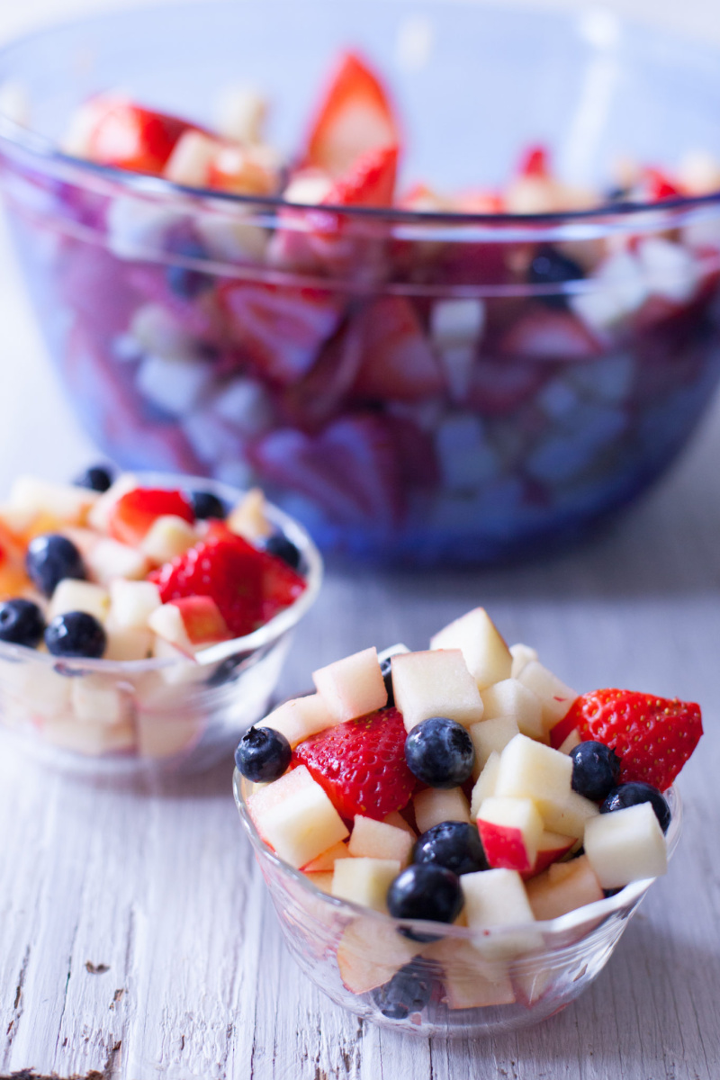 bowl of red white and blue fruit salad with two individual servings displayed