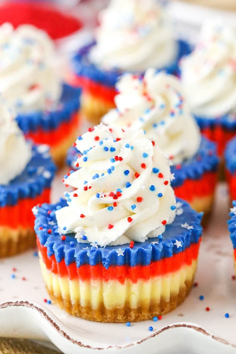 red white and blue mini cheesecakes with whipped cream