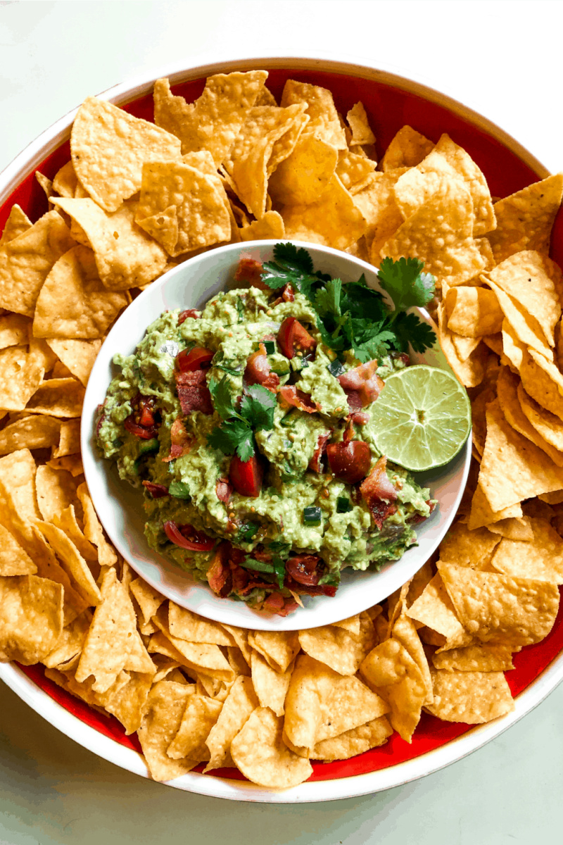 bacon guacamole in bowl surrounded by chips