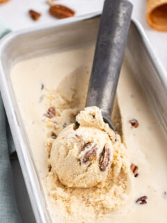 butter pecan ice cream in a container with an ice cream scoop