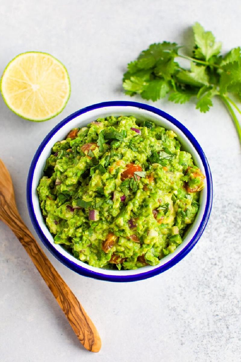 pea guacamole in a blue rimmed bowl