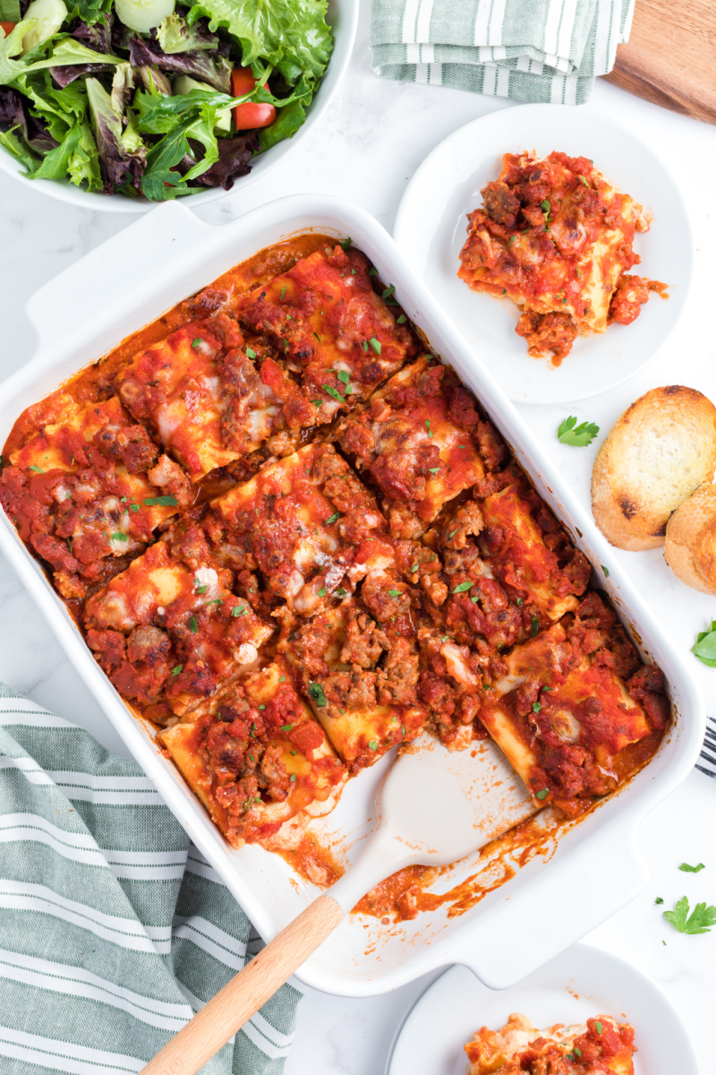 italian sausage lasagna rolls ups in a casserole dish with a couple taken out