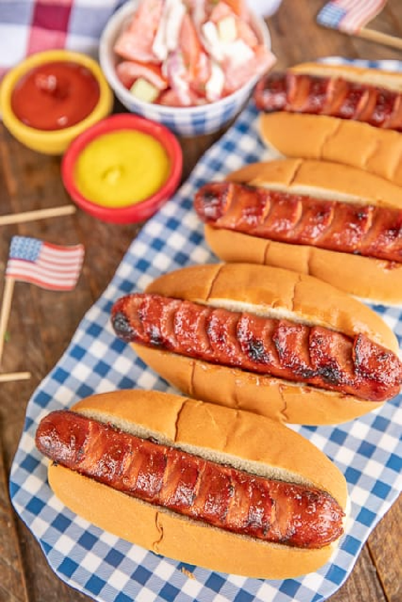 row of marinated grilled hot dogs on a blue and white checked platter