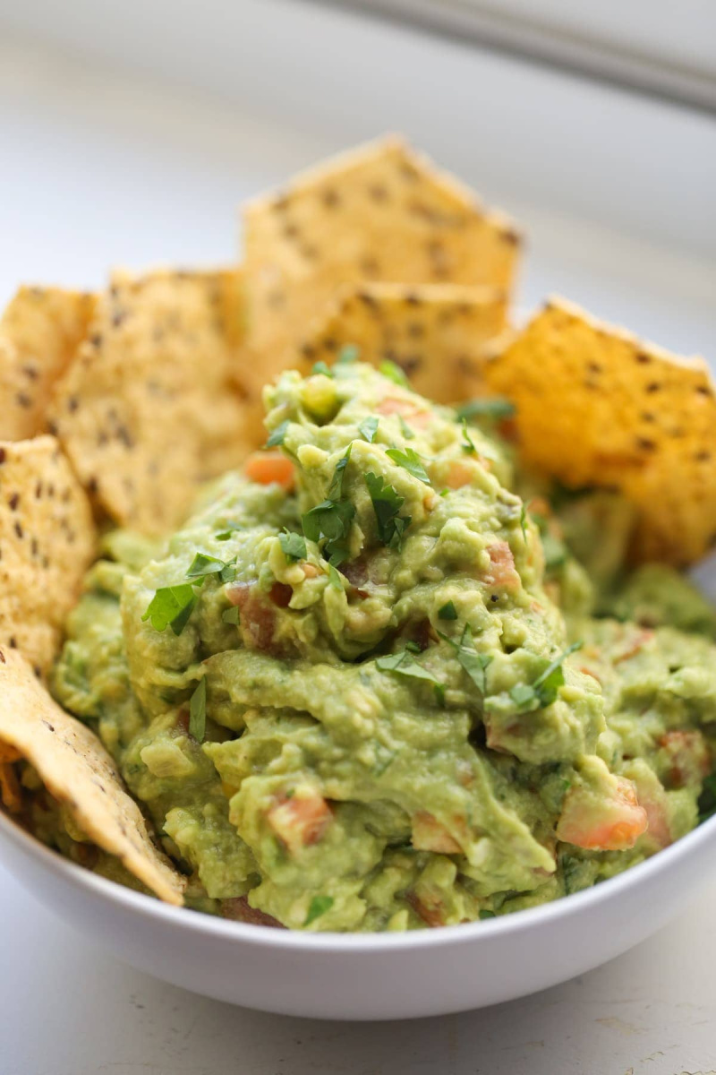 guacamole in a white bowl with chips