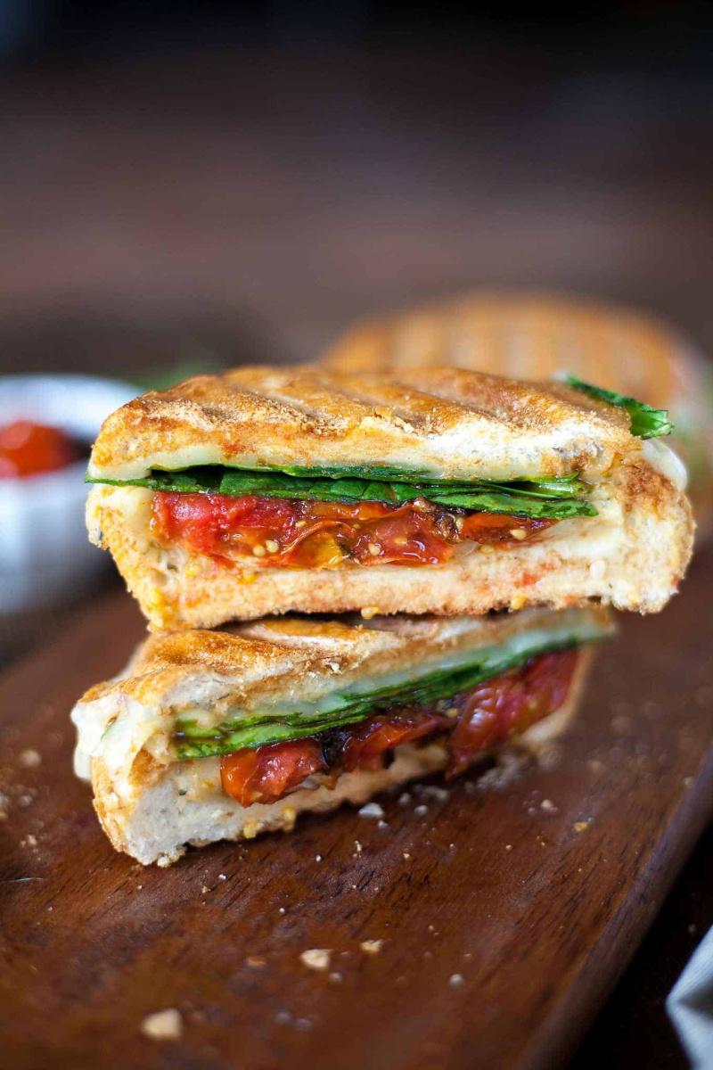 two slices stacked cheesy hummus veggie panini