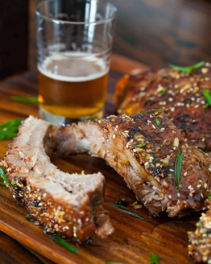 korean bbq baby back ribs on a cutting board with glass of beer