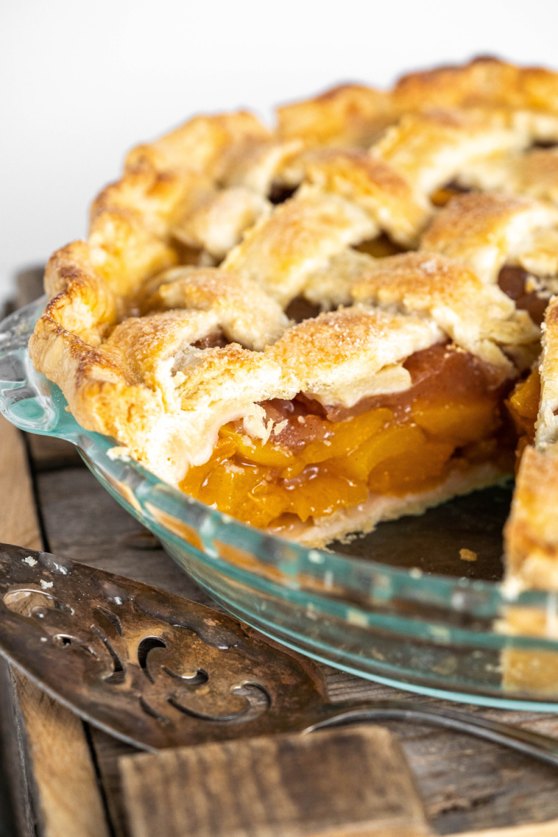 peach pie with slice cut out of it