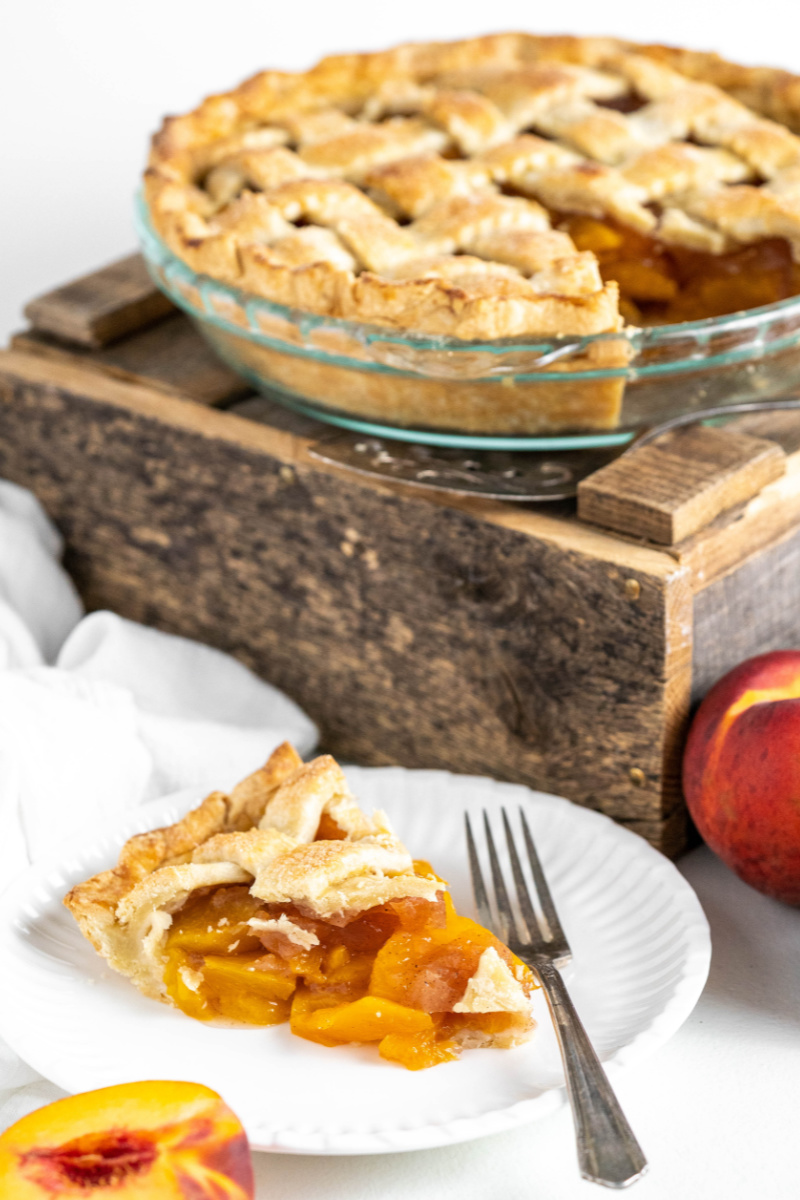 slice of peach pie with the rest of pie in background