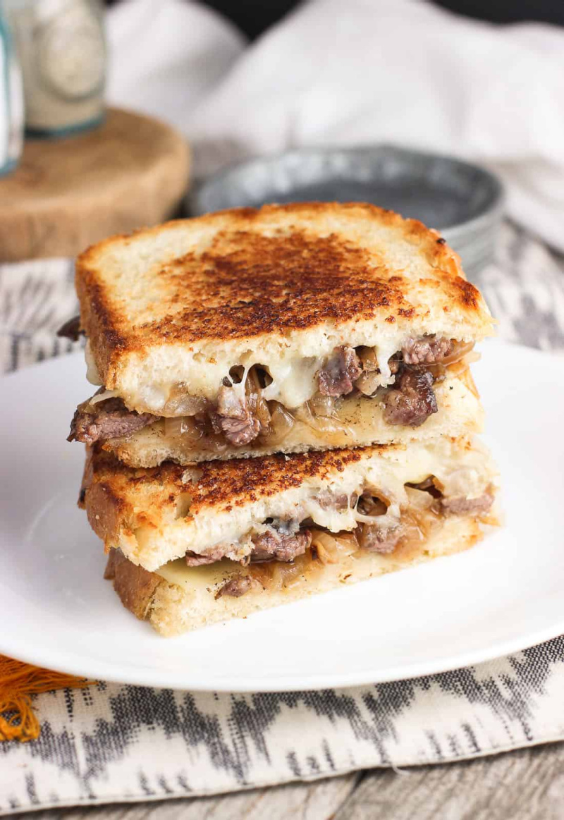 stacked philly cheesesteak panini on a white plate