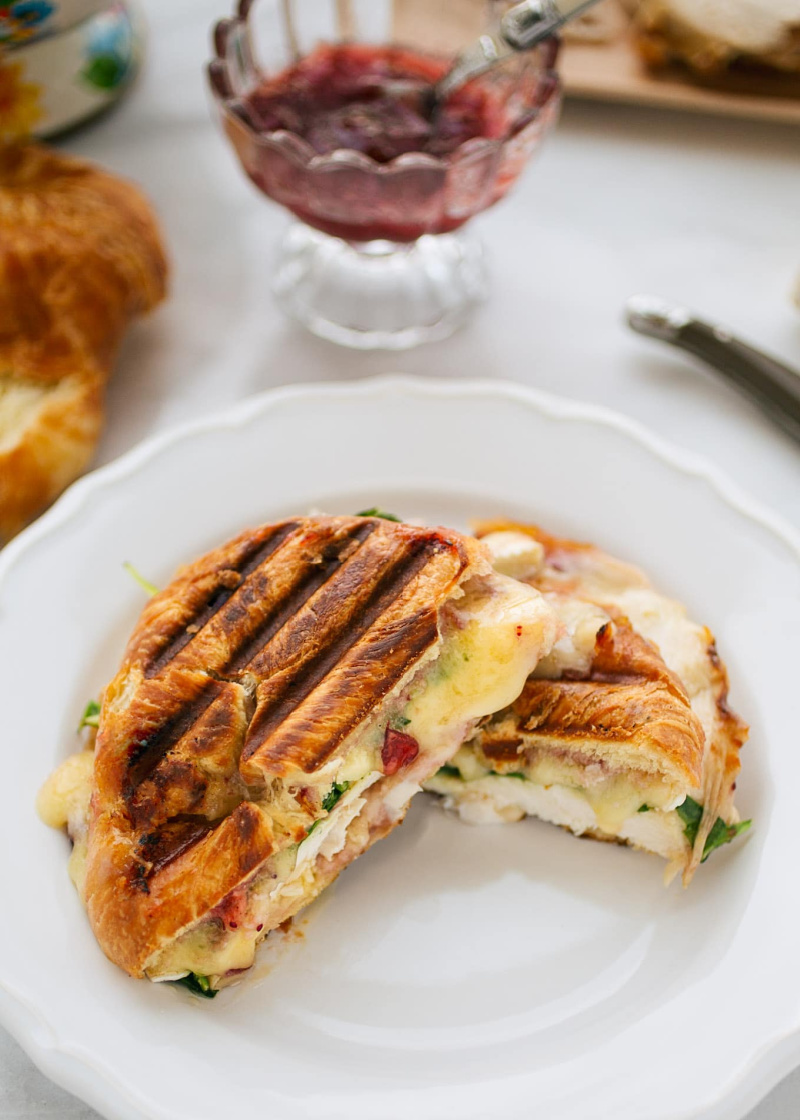 turkey and brie croissant panini on a white plate